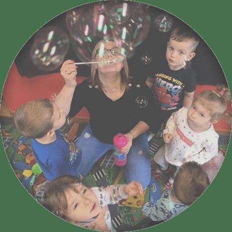Dzieci patrzące nakobietę dmuchającą bańki
